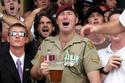 Punters and soldiers watch a Two Up game on Anzac day