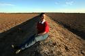 Rice farmer Robin Crawford sits amongst her drought ravaged paddies